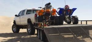 ATVs on Trailer Behind Pickup Truck